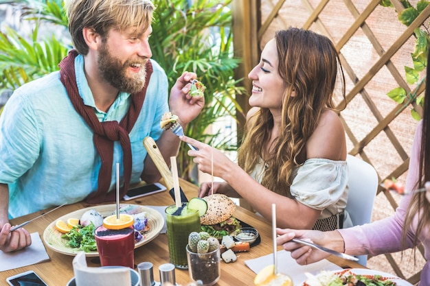 Jeune couple, manger un brunch et boire un bol de smoothie au bar vintage. des gens heureux ayant un déjeuner sain et discutant dans un restaurant branché