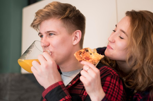 Jeune couple, manger pizza, chez soi