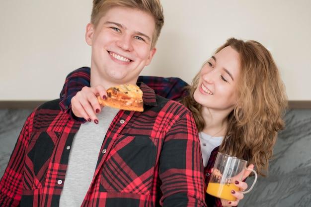 Jeune couple, manger pizza