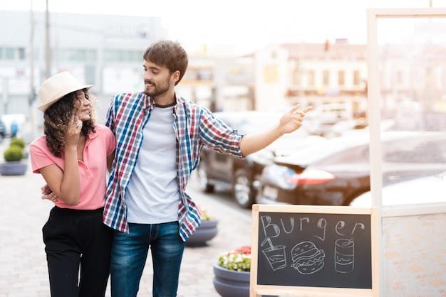 Jeune couple marchant au camion de nourriture sur la rue.