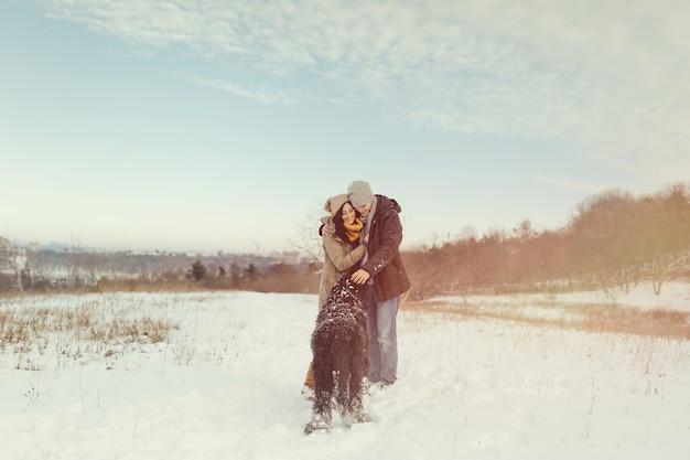 Jeune couple marchant avec un chien dans une journée d'hiver