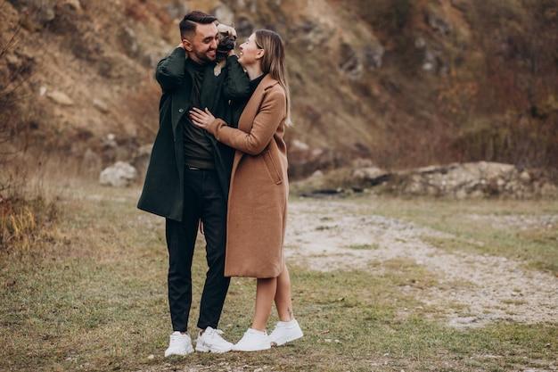 Jeune couple marchant leur bouledogue français dans le parc