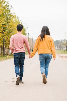 Jeune couple marchant le long de la route