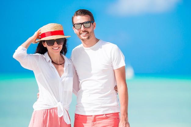 Jeune couple marchant sur une plage tropicale