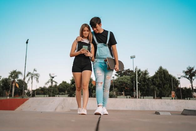 Jeune couple marchant, portant une planche à roulettes et regardant leur téléphone portable dans le parc.