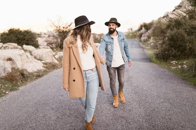 Jeune couple marchant sur la route de montagne