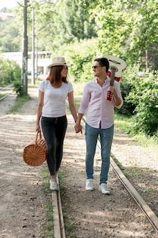 Jeune couple marchant sur une voie ferrée