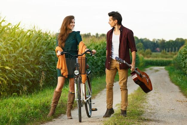 Jeune couple marche par une route de campagne