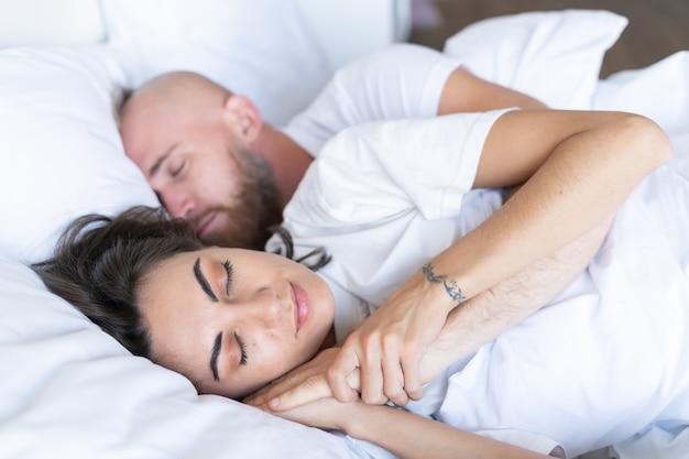 Jeune couple mari avec femme à la maison au lit dormant paisiblement dans une étreinte
