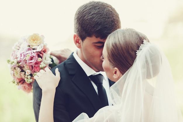 Jeune couple de mariage appréciant des moments romantiques en plein air se bouchent