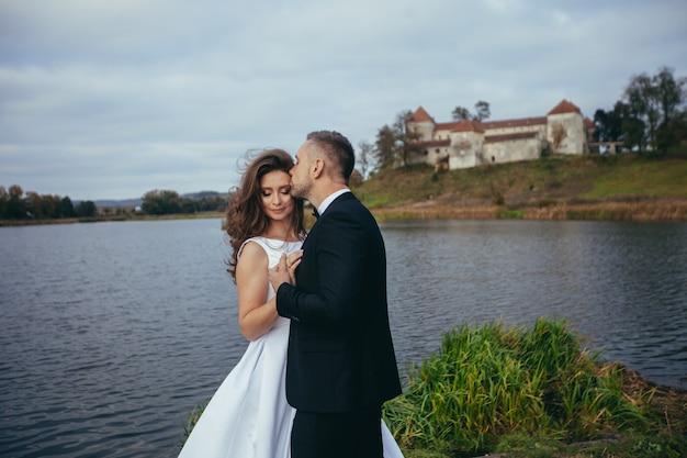 Jeune couple de mariage heureux étreindre et s'embrasser sur le fond du château et du lac en automne
