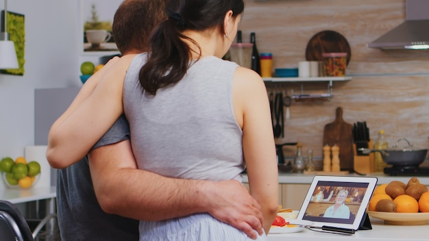 Jeune couple marié en appel vidéo avec sa mère pendant le petit-déjeuner dans la cuisine. jeune couple en pyjama utilisant la technologie internet en ligne pour discuter avec des parents et des amis