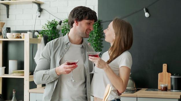 Jeune couple marié boit des cocktails dans la cuisine à la maison