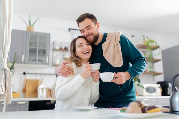 Jeune couple marié boit du café dans la cuisine