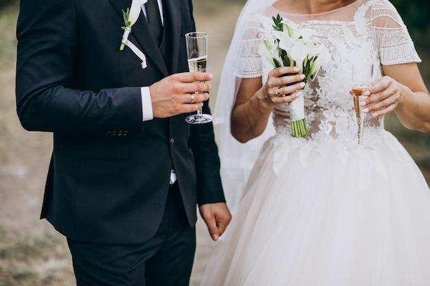 Jeune couple marié buvant du champagne ensemble