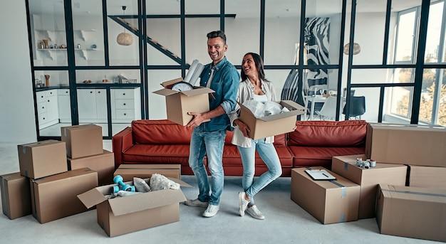 Un jeune couple marié dans le salon de la maison déballe des cartons avec des objets. heureux mari et femme s'amusent, attendent avec impatience une nouvelle maison. déménagement, achat d'une maison, concept d'appartement.
