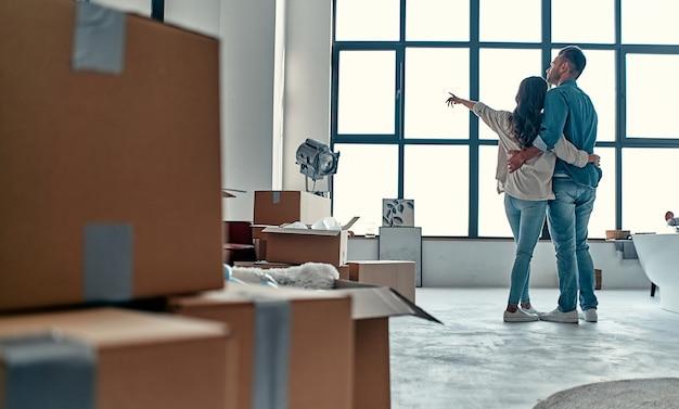 Un jeune couple marié dans le salon de la maison déballe des cartons avec des objets