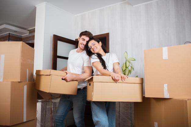Jeune couple marié dans le salon de la maison se tient près des boîtes déballées. ils sont contents de leur nouvelle maison. déménagement, achat d'une maison, concept d'appartement.