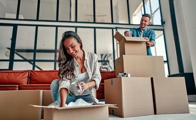 Un jeune couple marié déballant des objets dans des cartons dans le salon déménagement achetant une maison