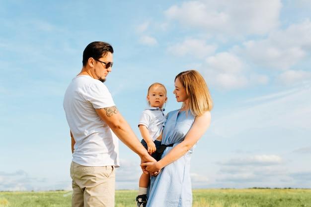 Jeune couple marié avec enfant dans un champ à l'extérieur, mari à lunettes tient sa femme par la main, mère tient son petit fils dans ses bras, regarde la caméra. portrait de famille, couple avec mode de vie bébé.