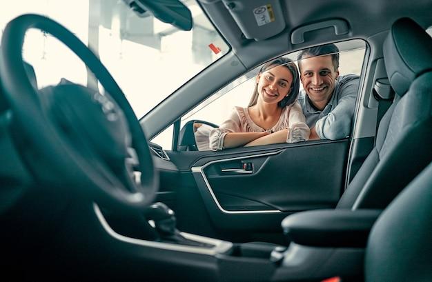 Jeune couple marié regarde dans une voiture chez un concessionnaire automobile. achat et location de voiture.
