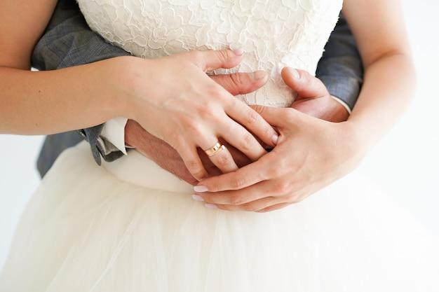 Jeune couple marié, tenant mains, à, anneaux, blanc, cérémonie, jour mariage