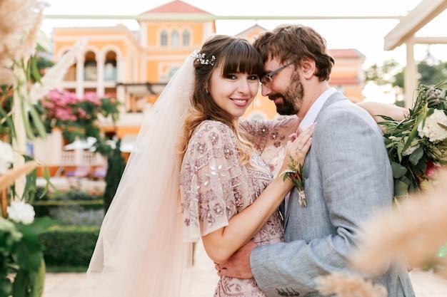 Jeune couple, mariée et le marié posant près de villa de luxe. décor de mariage. moments romantiques.