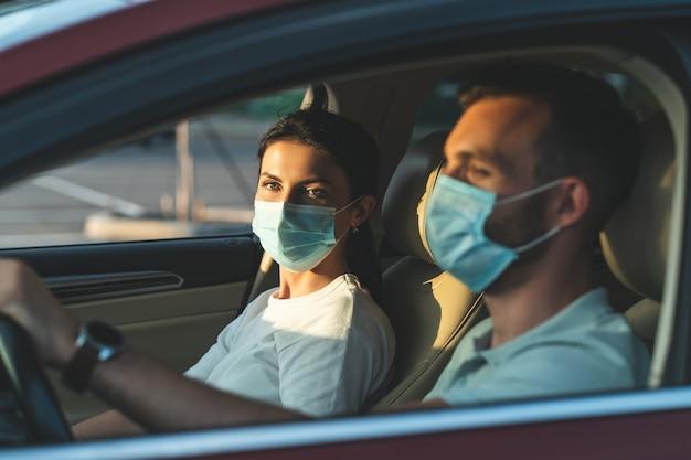 Le jeune couple masqué est assis dans la voiture