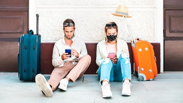 Jeune couple avec masque facial à l'aide de téléphones intelligents mobiles