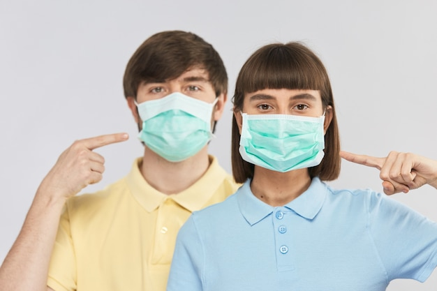 Jeune couple en masque facial de protection regardant la caméra et pointant dessus, protection anti coronavirus
