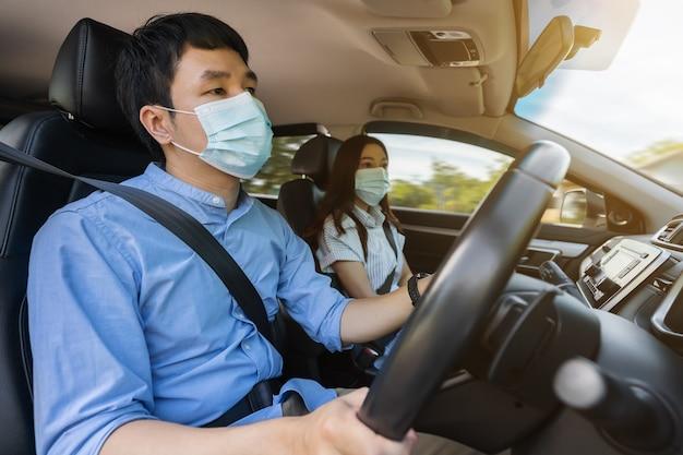 Jeune couple en masque médical en conduisant une voiture. pour protéger la pandémie de covid-19 (coronavirus)