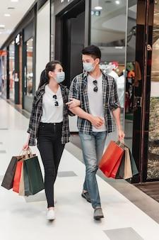 Jeune couple en masque de protection tenant plusieurs sacs en papier marchant dans le couloir du grand centre commercial