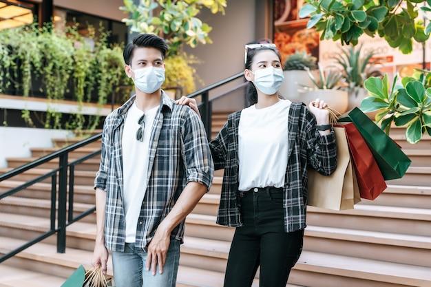 Jeune couple en masque de protection tenant plusieurs sacs en papier