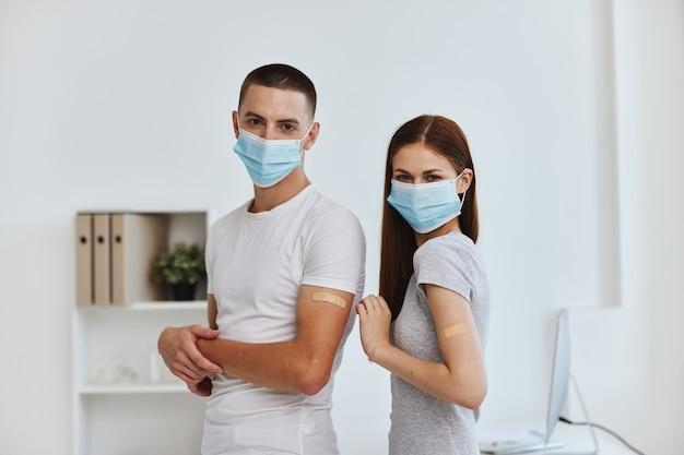 Jeune couple en masques médicaux pansements adhésifs sur les mains passeport vaccin lakhtine