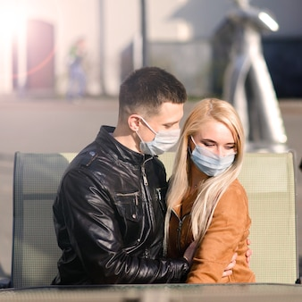 Jeune couple en masques sur la rue de la ville. isolement, quarantaine.