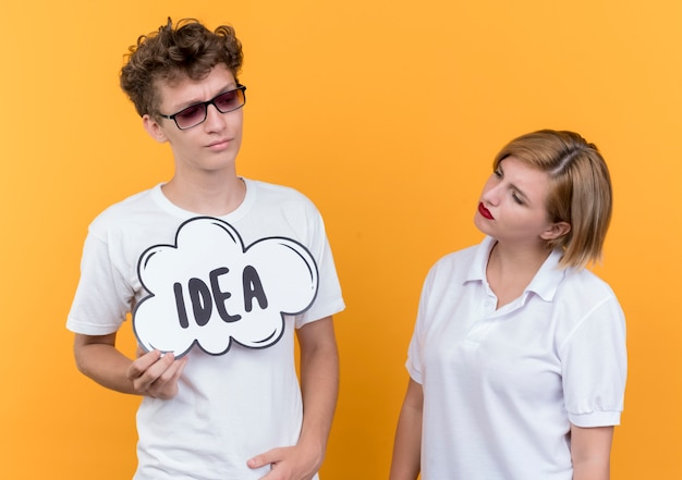 Jeune couple mécontent de l'homme tenant le signe de la bulle de dialogue avec l'idée de mot tandis que sa petite amie le regarde être confus debout sur un mur orange