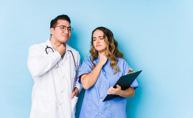 Jeune couple de médecins posant dans un mur bleu isolé souffre de douleurs à la gorge en raison d'un virus ou d'une infection.