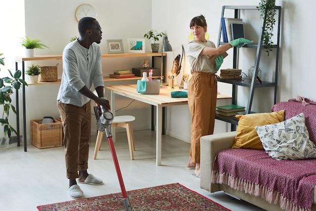 Jeune couple ménage ensemble jeune homme à l'aide d'un aspirateur et femme essuyant la poussière
