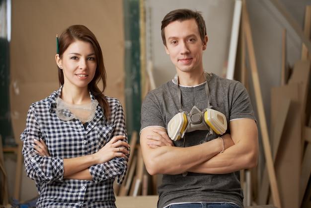 Jeune couple menuisiers avec les bras croisés en regardant la caméra en atelier