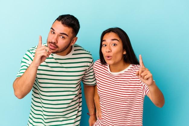 Jeune couple métis isolé sur bleu ayant une idée, concept d'inspiration.
