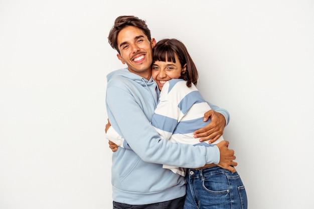 Jeune couple métis isolé sur fond blanc câlins, souriant insouciant et heureux.