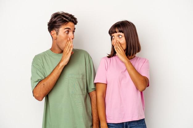 Jeune couple métis isolé sur fond blanc choqué à cause de quelque chose qu'elle a vu.