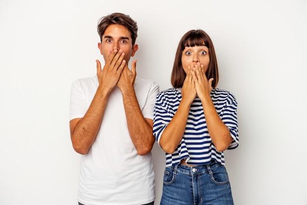 Jeune couple métis isolé sur fond blanc choqué, se couvrant la bouche avec les mains, impatient de découvrir quelque chose de nouveau.