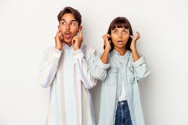 Jeune couple métis isolé sur fond blanc couvrant les oreilles avec les doigts, stressé et désespéré par une ambiance bruyante.