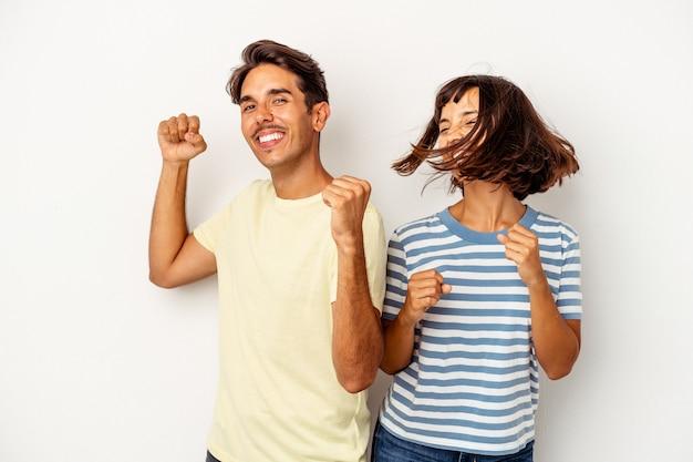 Jeune couple métis isolé sur fond blanc dansant et s'amusant.