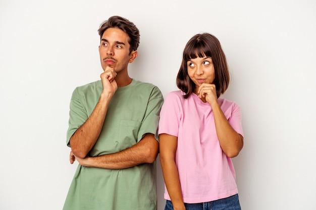 Jeune couple métis isolé sur fond blanc détendu en pensant à quelque chose en regardant un espace de copie.