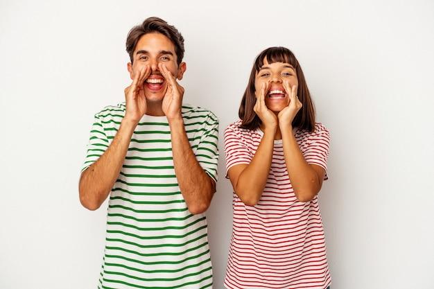 Jeune couple métis isolé sur fond blanc disant un potin, pointant vers le côté rapportant quelque chose.