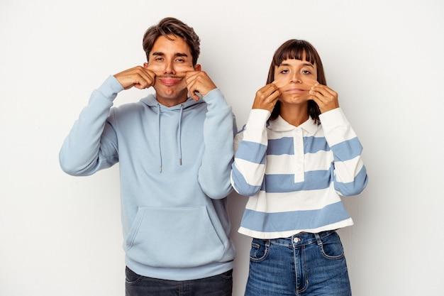 Jeune couple métis isolé sur fond blanc doutant entre deux options.