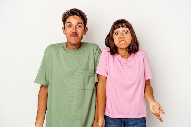 Jeune couple métis isolé sur fond blanc hausse les épaules et ouvre les yeux confus.