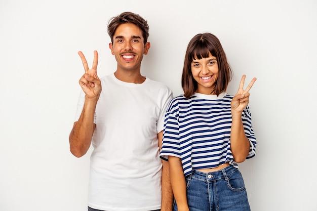 Jeune couple métis isolé sur fond blanc joyeux et insouciant montrant un symbole de paix avec les doigts.